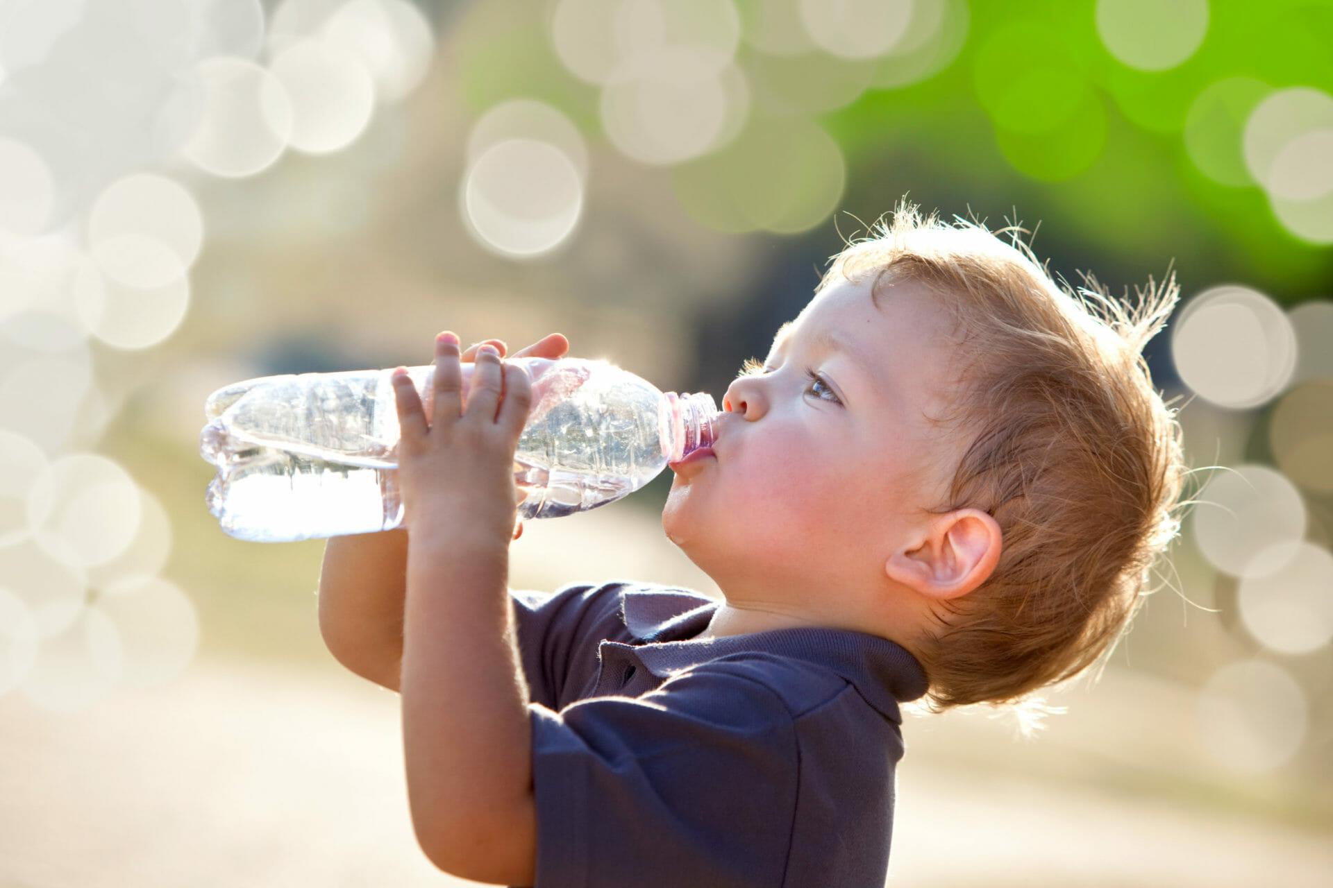 beautiful blonde child drink water outdoor